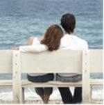 Pareja sentados mirando el mar